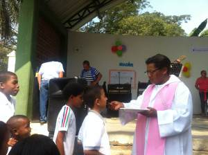 Dando la Eucaristía a los niños de Colegio Educativo Navarro